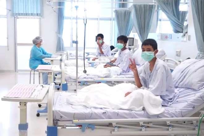 Jovens acenam em hospital da Tailândia - AFP